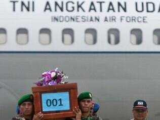 Militares indonésios carregar o caixão de uma vítima no acidente aéreo da AirAsia