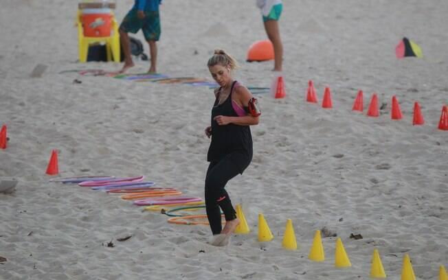 Carolina Dieckmann se exercita com personal na praia