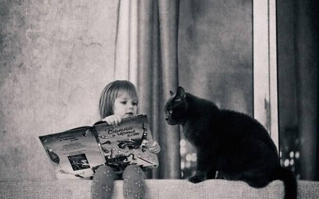 Menina contando uma história pro seu lindo gato preto.