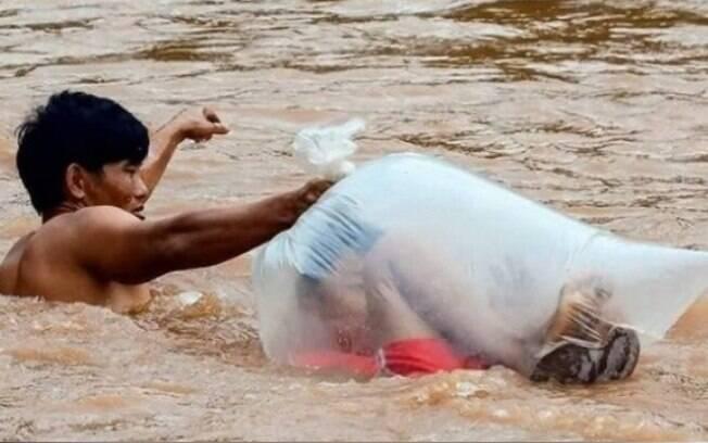 Aldeões fazem a travessia das crianças a nado no Vietnã
