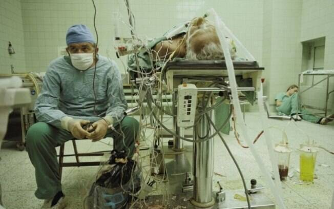Cirurgião depois de uma cirurgia de sucesso para transplante de coração, que durou 23 horas. No canto da sala, sua assistente dorme em sono profundo; esgotada.