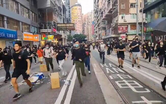 Manifestantes correm de gás lacrimogêneo lançado pela polícia
