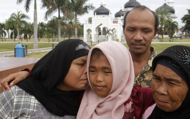 Jamaliah, à esq., beija a filha Raudhatul Jannah, 14, que reencontrou após dez anos. A menina sumiu durante o tsunami de 2004, em Banda Aceh (8/08). Foto: Reuters