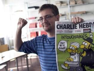 O diretor e chargista do Charlie Hebdo, Charb, segurando uma das capas polêmicas da publicação