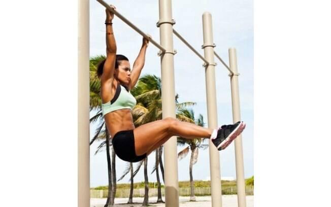 mulher fazendo elevaçào de pernas na barra