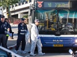 Israeli forensics examine the scene of an attack after a Palestinian man stabbed at least five people on a Tel Aviv bus on January 21, 2015. The attacker struck in the morning rush hour in the heart of Israel's commercial capital before being shot by a passing prison officer, Israeli police said. AFP PHOTO / JACK GUEZ