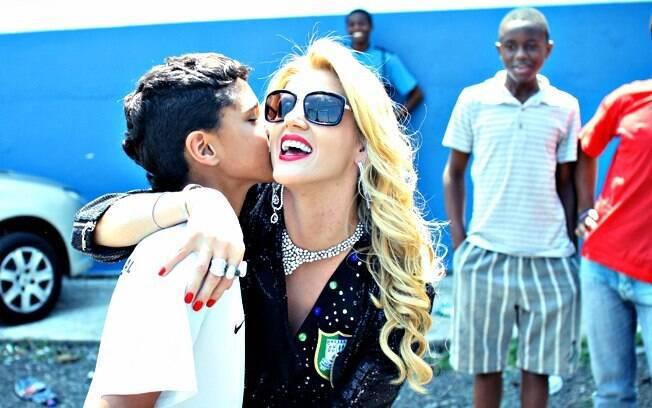 Depois de ser confundida com a Xuxa, a socialite posa com as crianças da Vila Maria