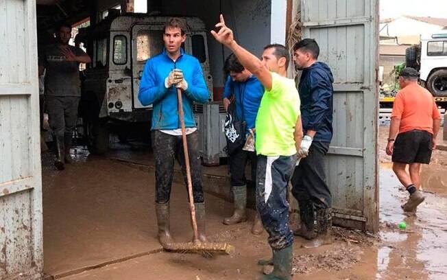 Rafael Nadal vestiu botas e pegou uma pá para ajudar a retirar a lama dos comércios da cidade