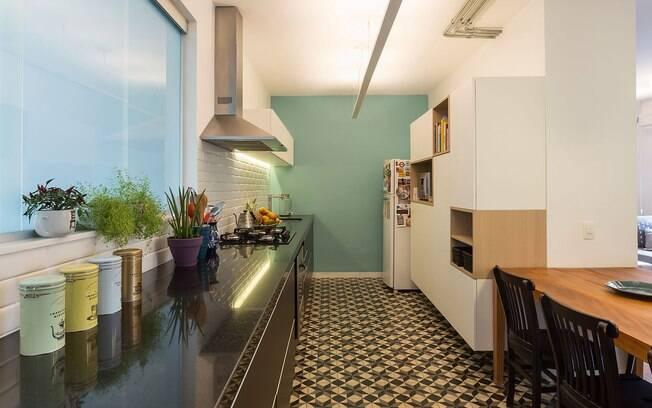 A parede azul e o ladrilho hidráulico preto e branco são as vedetes da cozinha que tem o restante dos acabamentos neutros