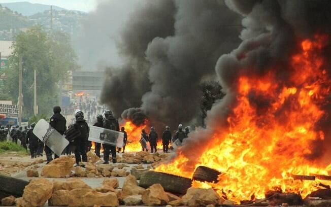 Policiais cruzam barricada deixada por manifestantes na cidade de Nochixtlan, em Oaxaca