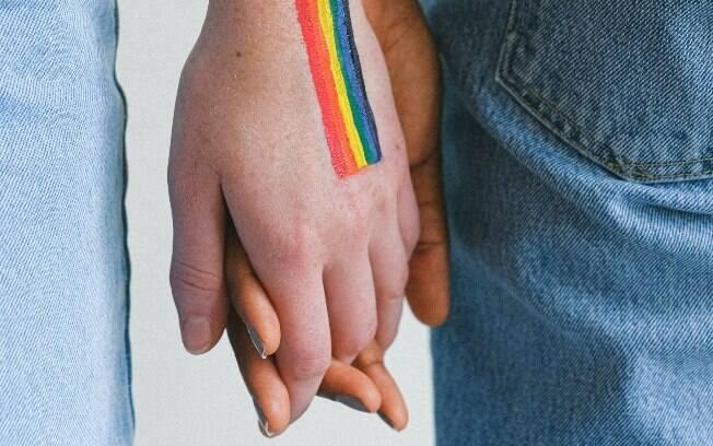 duas pessoas de mãos dadas; em uma das mãos, está uma bandeira