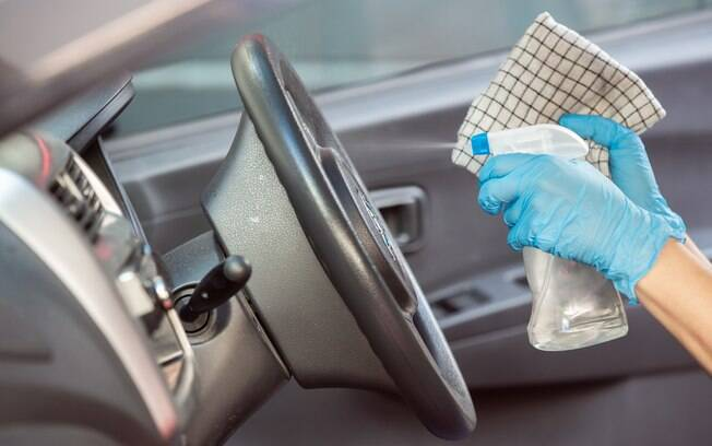 Pessoa higienizando o volante do carro com álcool e um pano descartável.
