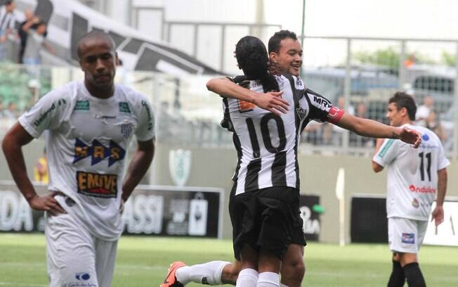 Rever é abraçado por Ronaldinho Gaúcho depois  de marcar para o Atlético-MG em cima do Tupi