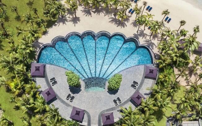 Na lista de fotos de piscinas, a piscina em formato de concha é uma boa opção para entrar no clima de praia