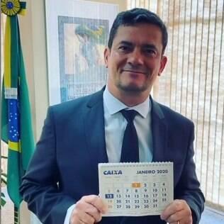 Sergio Moro sorrindo e segurando um calendário