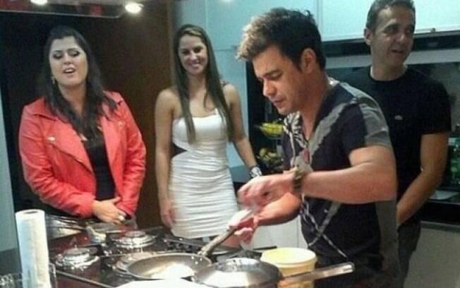 Zezé di Camargo prepara prato durante refeição na casa de um dos patrocinadores de show em Minas Gerais. Gracielle (de vestido branco) aparece logo atrás