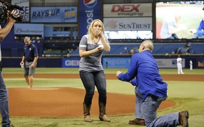 Cameron se ajoelha e entrega para Melissa uma bola de beisebol escrita