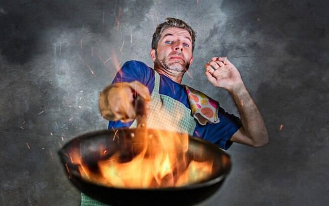 Homem assustado segurando frigideira em chamas