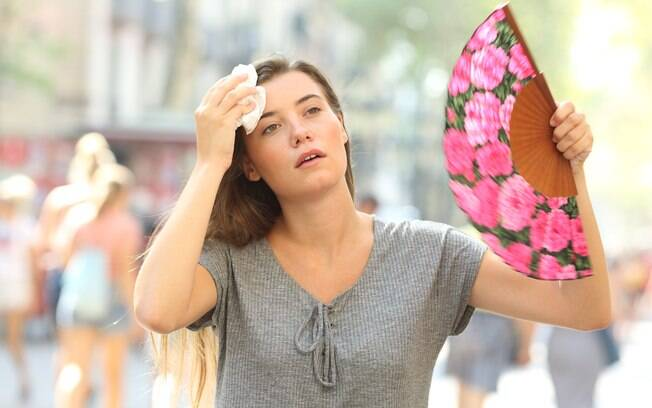 Mulher secando a testa com um lenço e se abanando com um leque