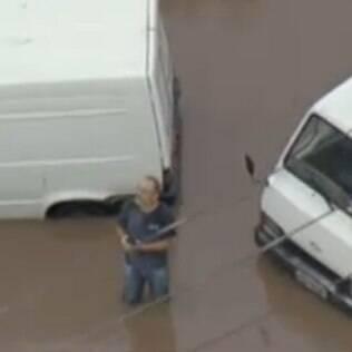 Homem enfrenta enchente na zona sul de São Paulo na segunda-feira (12)