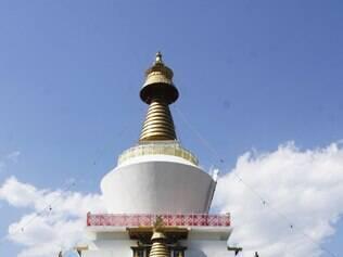 Butaneses caminham ao redor da estupa (espiral dourada) no Memorial de Chorten