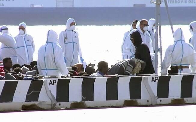 Imigrantes recebem ajuda de profissionais de resgate médico no porto italiano de Messina. Foto: AP/Reprodução de TV