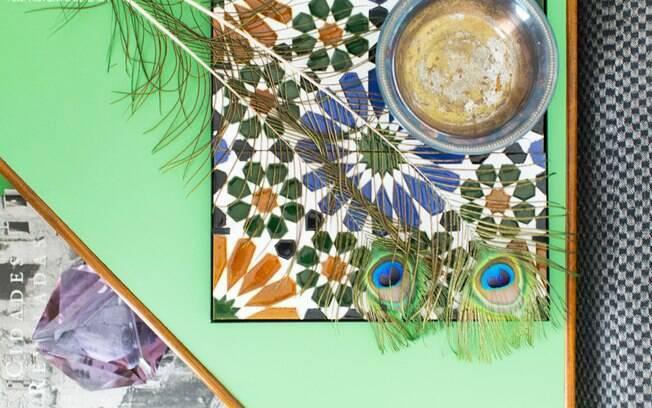 A bandeja em azulejo colocada sobre a mesa verde traz um contraste vivo de cores. Serve de apoio e ao mesmo tempo é um dos belos detalhes na decoração