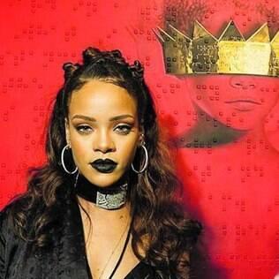 """Álbum. Rihanna posa ao lado da capa de """"ANTI"""", em que surge uma imagem dela mesma criança"""