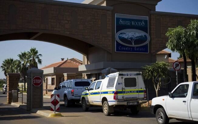 Carros de polícia são vistos na entrada do  condomínio de Oscar Pistorius na cidade de  Pretoria