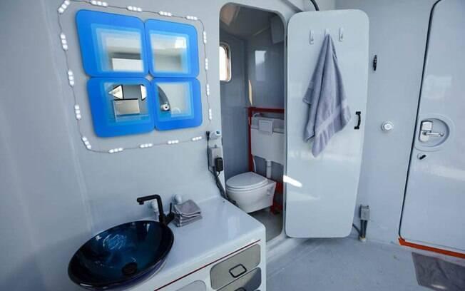 Atrás de uma porta com bordas arredondadas (como as de uma nave), há um pequeno banheiro