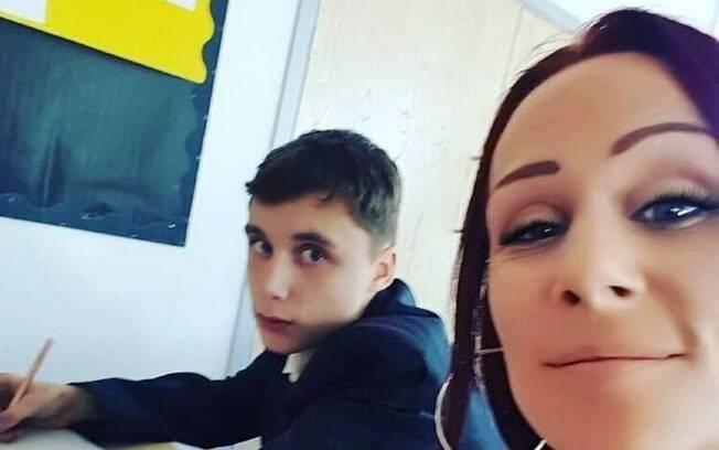 mãe assiste aula ao lado do filho para dar uma lição nele