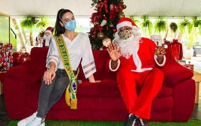 Miss Brasil e Papai Noel posam para foto em evento beneficente