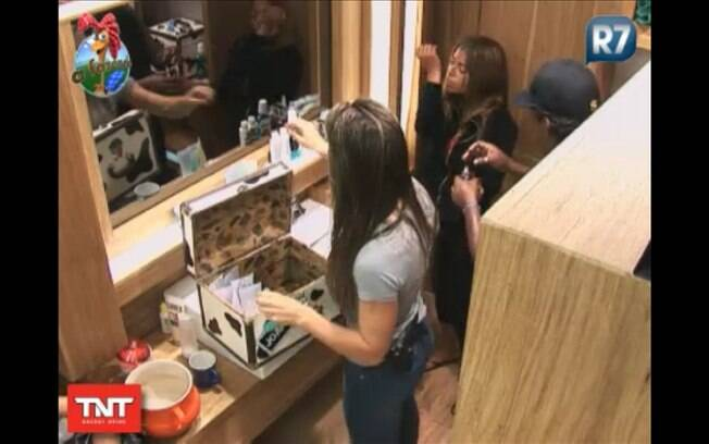 Joana guarda seus produtos e Compadre mostra seu perfume para Raquel, que experimenta no pulso e cheira