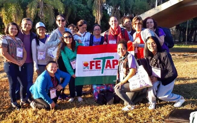 Mulheres seguram a bandeira da Federação dos Trabalhadores Rurais Agricultores e Agricultoras Familiares de Pernambuco (Fetape)