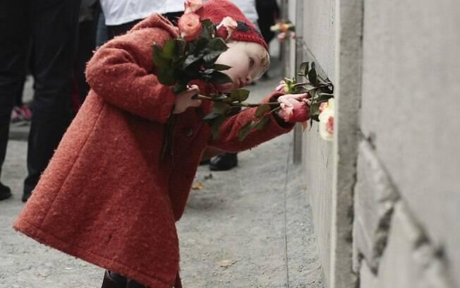 Menina de três anos deixa flores em parte do antigo muro de Berlim