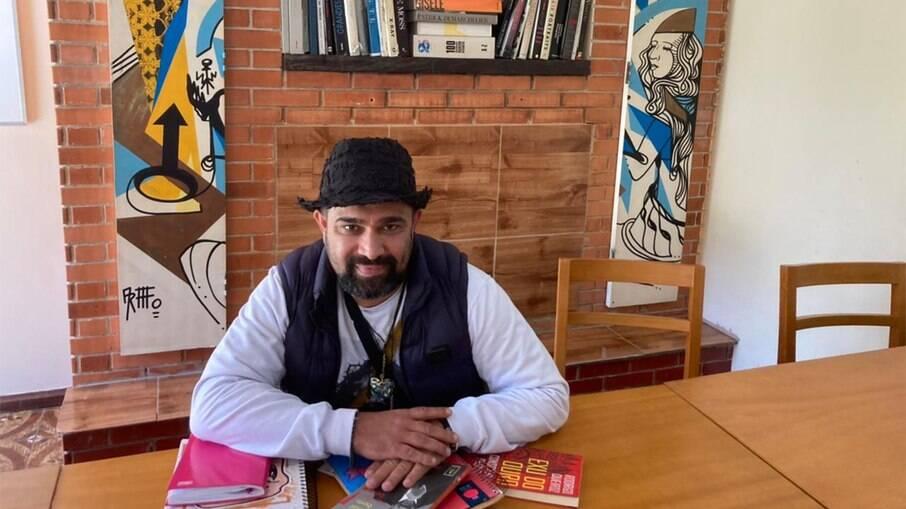 Evandro Santo com os livros e o caderno onde escreve todas as noites. Ao fundo, livros e quadros que ele doou para a clínica