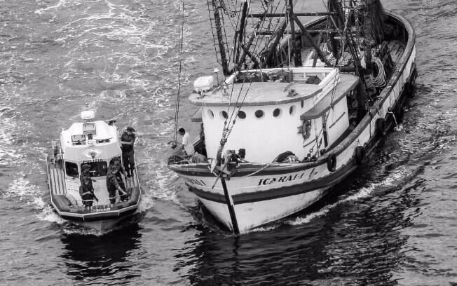 Lancha da Polícia Militar Ambiental fazendo abordagem de rotina em barco pesqueiro