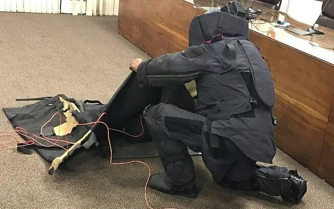 Após o GATE determinar o tipo de bomba e seu mecanismo de detonação, o Explosivista volta para o auditório e coloca uma segunda bomba, feita pelo GATE, dentro da mochila, que ao ser detonada irá desativar a bomba original. Note que tudo está sendo coberto por uma manta balística para minimizar os efeitos da explosão. Sem proteção nas mãos, o Explosivista manipula agora duas bombas