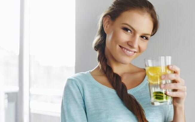 mulher segurando copo com água com limão