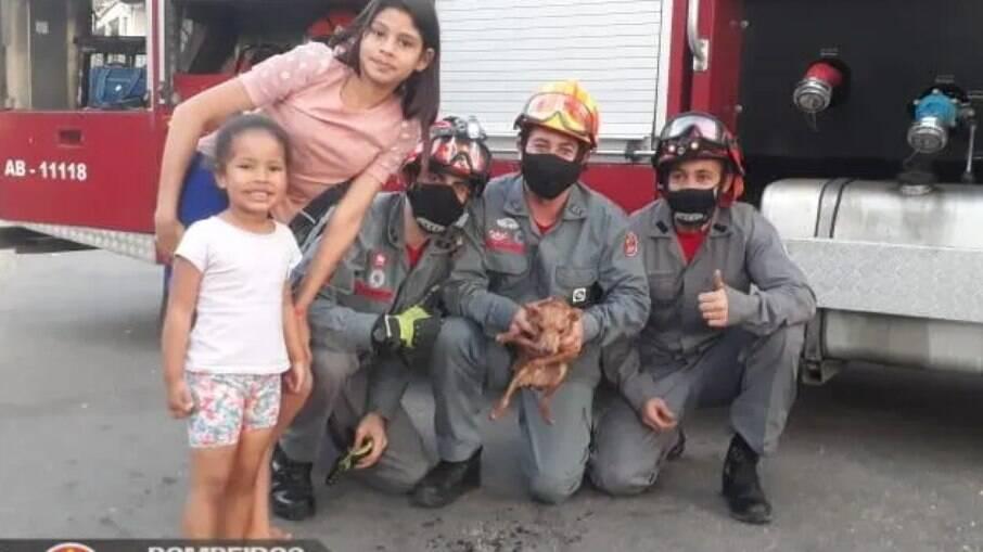 Os bombeiros ao lado da família do cãozinho resgatado