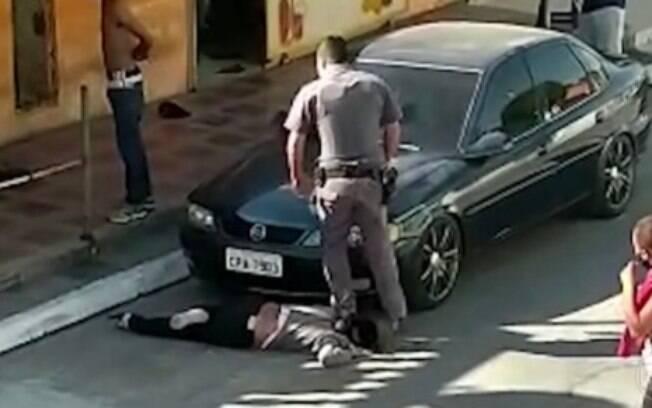 As imagens mostram os policiais rendendo um homem e apontando arma para outro, além das agressões à comerciante