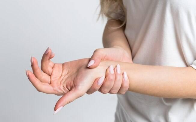 Mulher segurando a mão adormecida