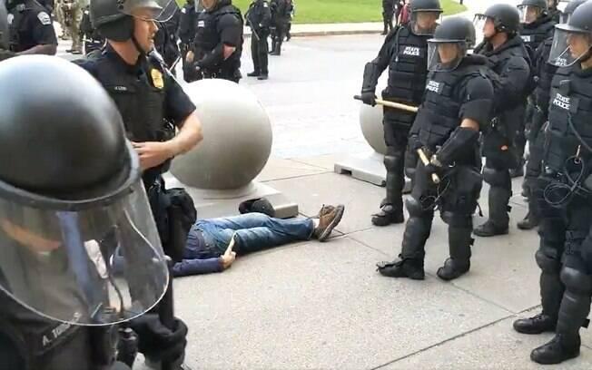 homem deitado no chão cercado por policiais