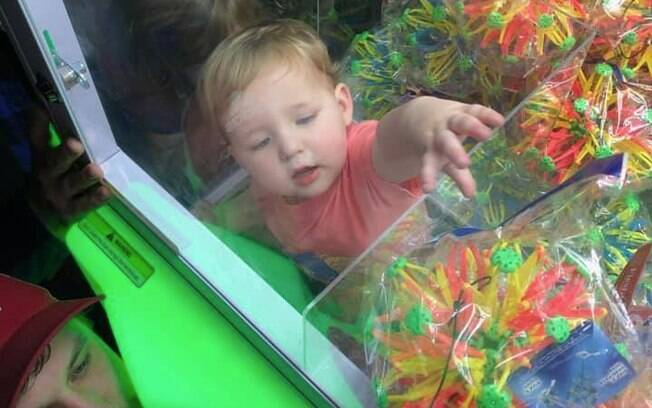 Menino não parecia nenhum um pouco incomodado por estar preso na máquina de pegar brinquedo