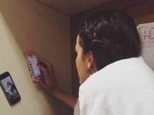 Atriz foi clicada de roupão interagindo em três celulares, nos bastidores de