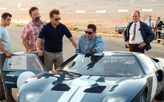 De camisa polo azul, Matt Damon interpreta Carrol Shelby e, de luvas, Christian Bale vive o piloto Ken Miles no premiado Ford vs. Ferrari