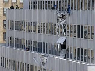 Bombeiros examinam danos causados à fachada do edifício por acidente com guindaste