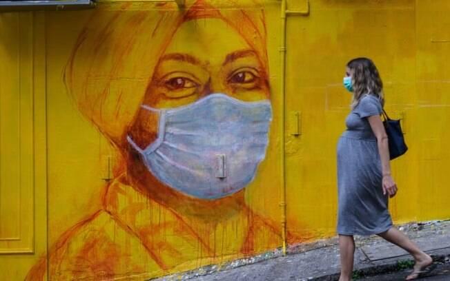 Uma mulher grávida%2C usando uma máscara facial como medida de precaução%2C passa por um mural de rua em Hong Kong