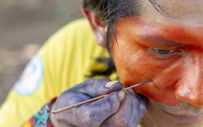 Indígena Huni Kuin se pintando