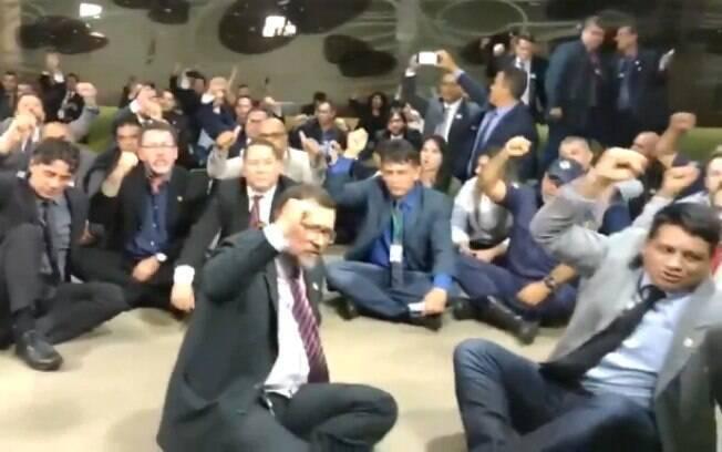 Sentados no chão, delegados chamam o presidente Jair Bolsonaro (PSL) de traidor por causa da reforma da Previdência